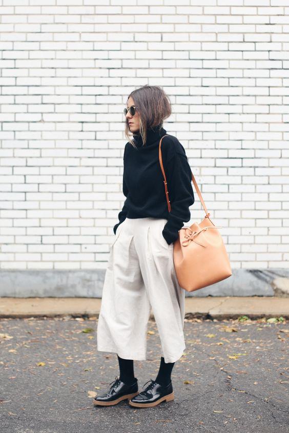 calça pantacourt clara, blusa preta e bolsa saco