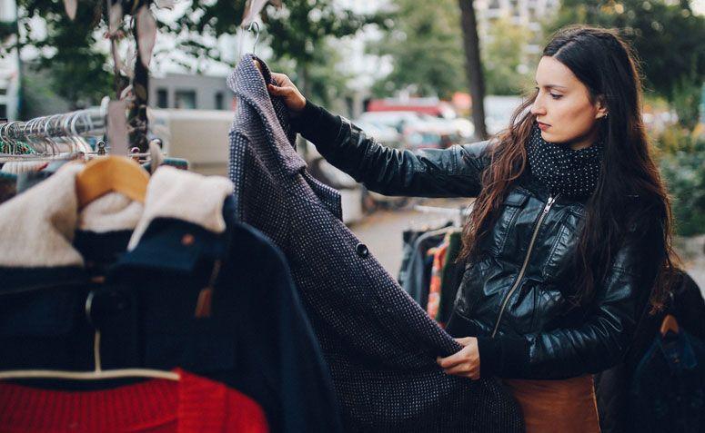 mulher segurando casaco de inverno brechó