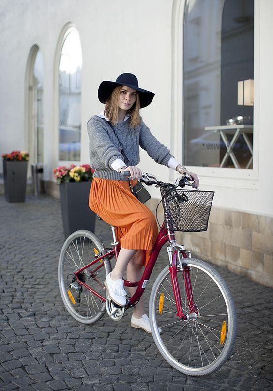 saia plissada laranja, casaco cinza e chapéu look bicicleta