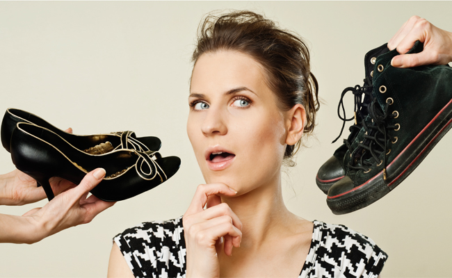 mulher em dúvida entre sapato de salto lto e tênis all star para viajar