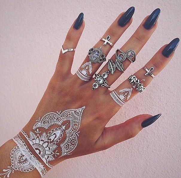 tatuagem temporária de henna branca que imita renda nas mãos e pulso