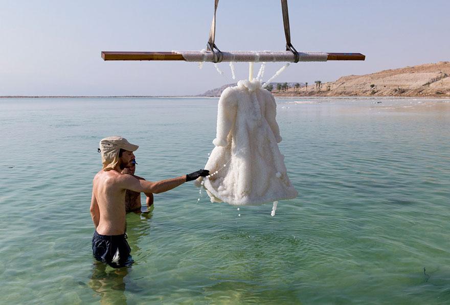 homem deixa vestido por 2 anos no mar morto foto retirando o vestido do mar