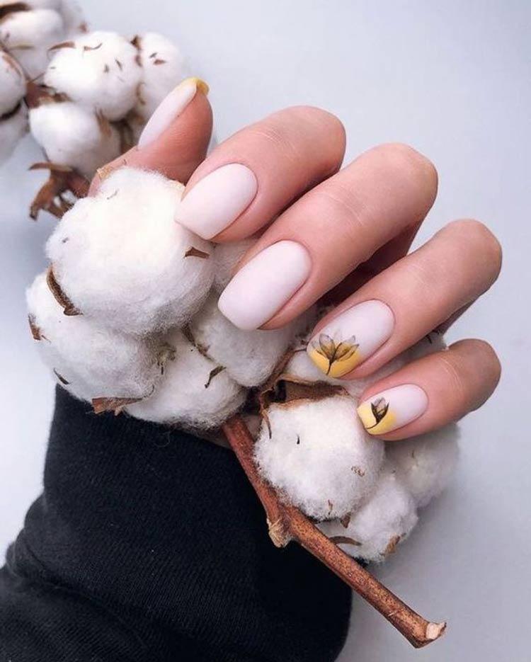 Manicure-rosa-claro-decorado-com-meias-luas-amarelas-e-flores-de-algodão