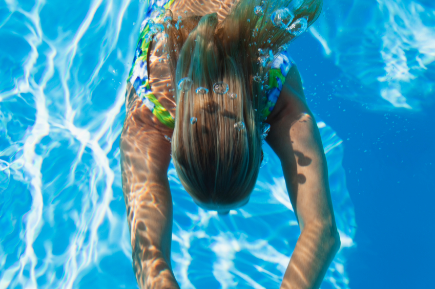 Swimming pool, woman swimming under water