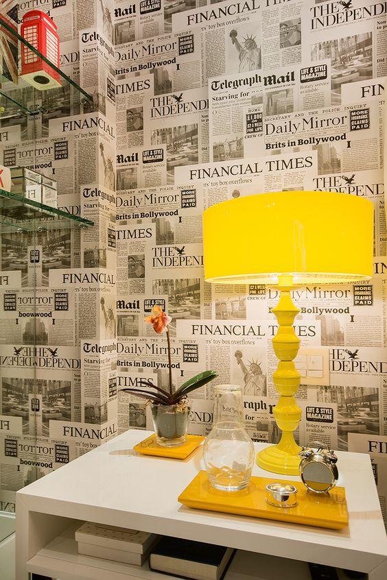 decoração de parede com jornal e abajour amarelo