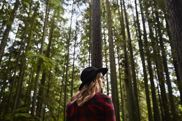 banho de floresta mulher de chapéu no meio da natureza