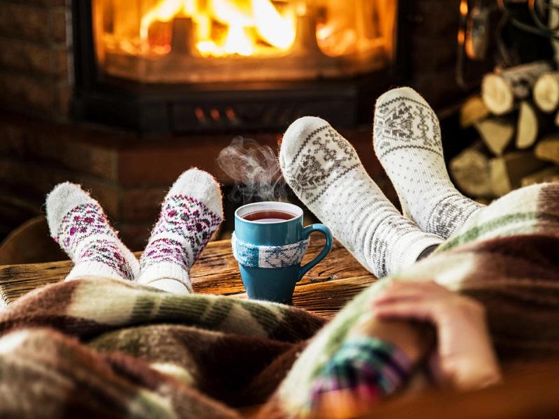 hygge sentado na frente da lareira com meias de lã