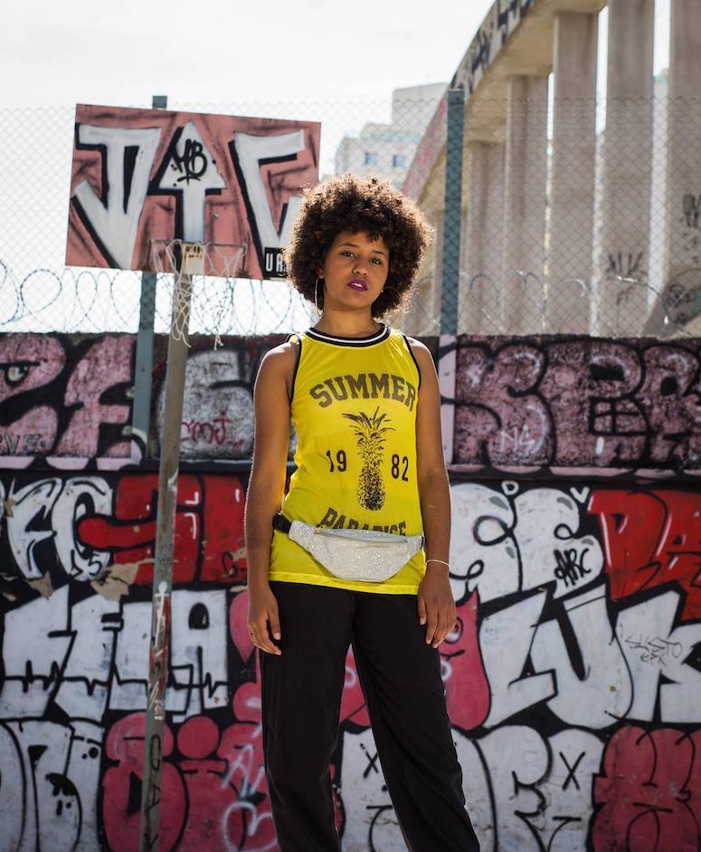 look calça preta, camiseta regata amarela e pochete de glitter