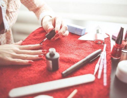mulher pintando as unhas de vermelho