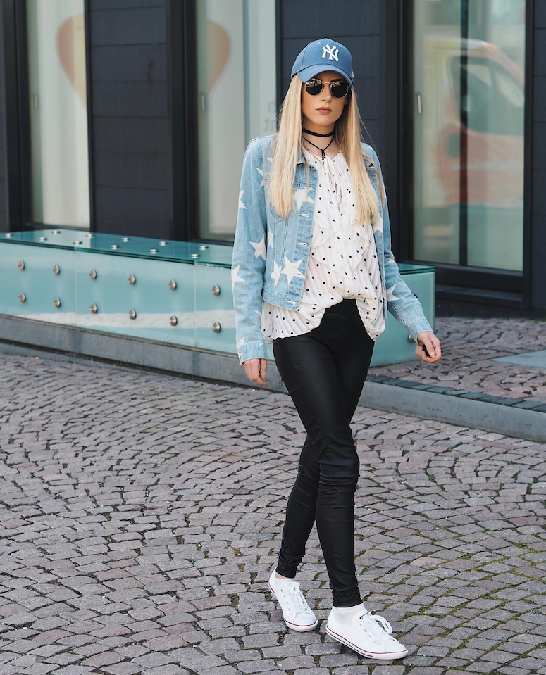 looks com boné feminino calça preta com blusa de bilinhas e jaqueta jeans