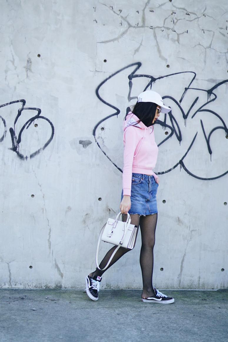 looks com boné feminino saia jeans com meia-calça arrastão e moletom rosa com bolsa branca