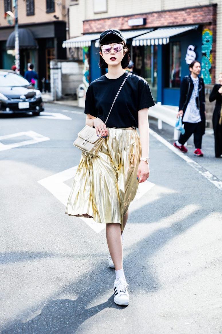 looks com boné feminino saia plissada dourada metalizada e camiseta