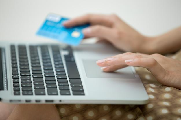 mulher com notebook no colo e cartão de crédito nas mãos compras pela internet