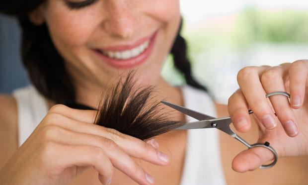 mulher cortando as pontas dos cabelos com tesoura