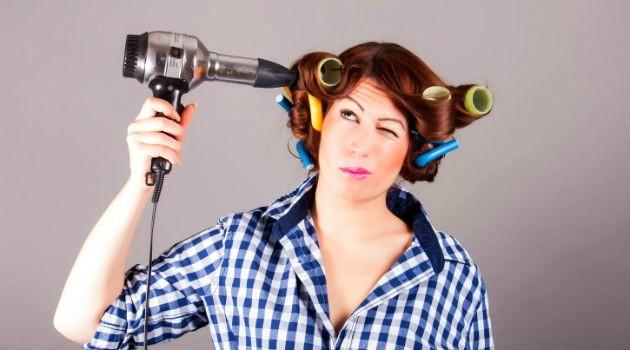 mulher secando os cabelos com bobs na cabeça e camisa xadrez vichy