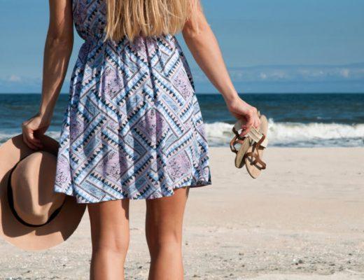 mulher com os pés na areia da praia segurando chapéu