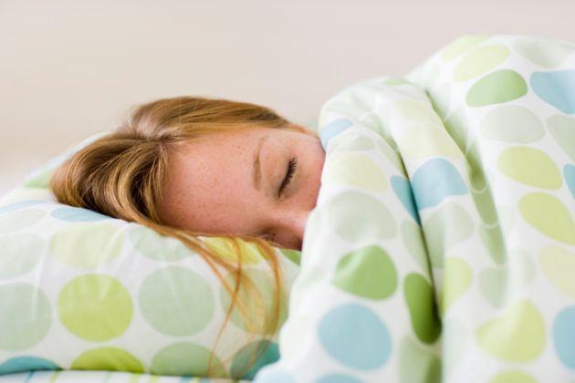 mulher deitada na cama com coberta cobrindo o rosto