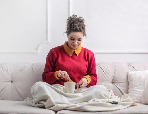 mulher sentada no sofá comendo e molhando bolacha no café