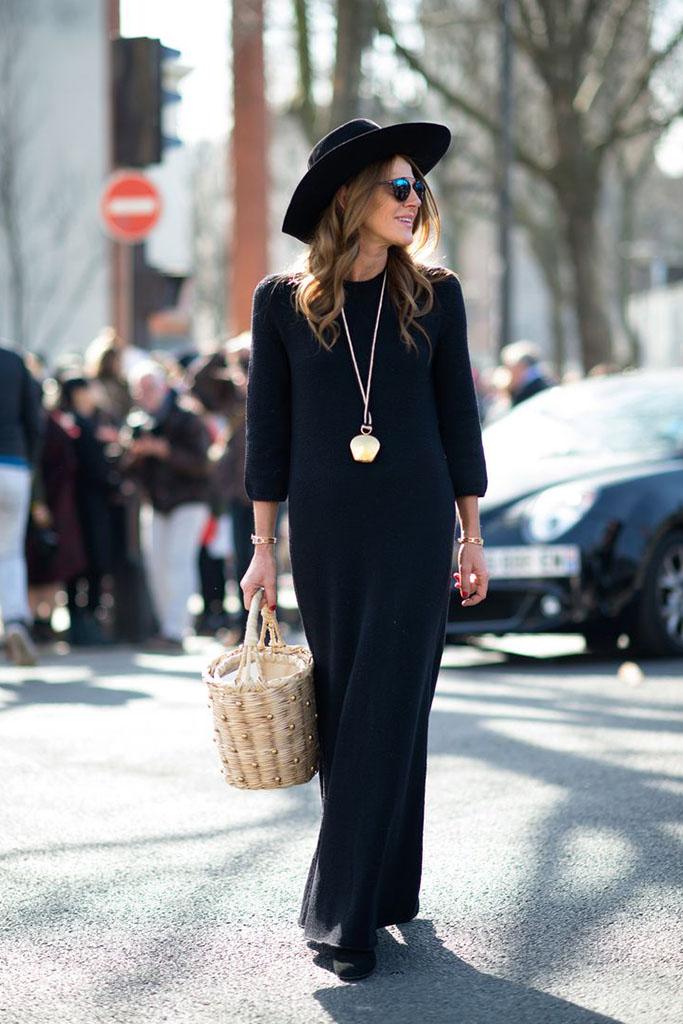 vestido longo preto com bolsa de palha e chapéu preto