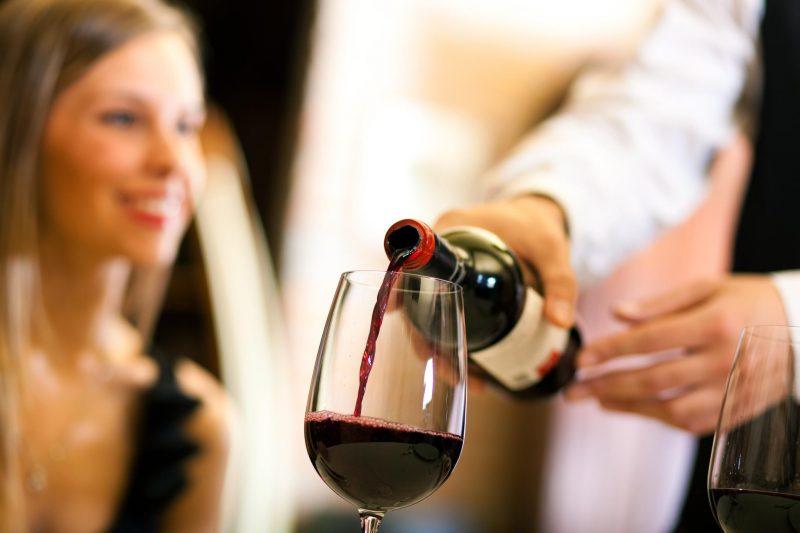 servindo vinho tinto para mulher