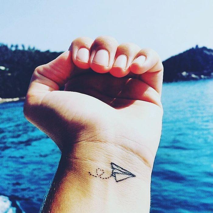 tatuagem de avião de papel no pulso