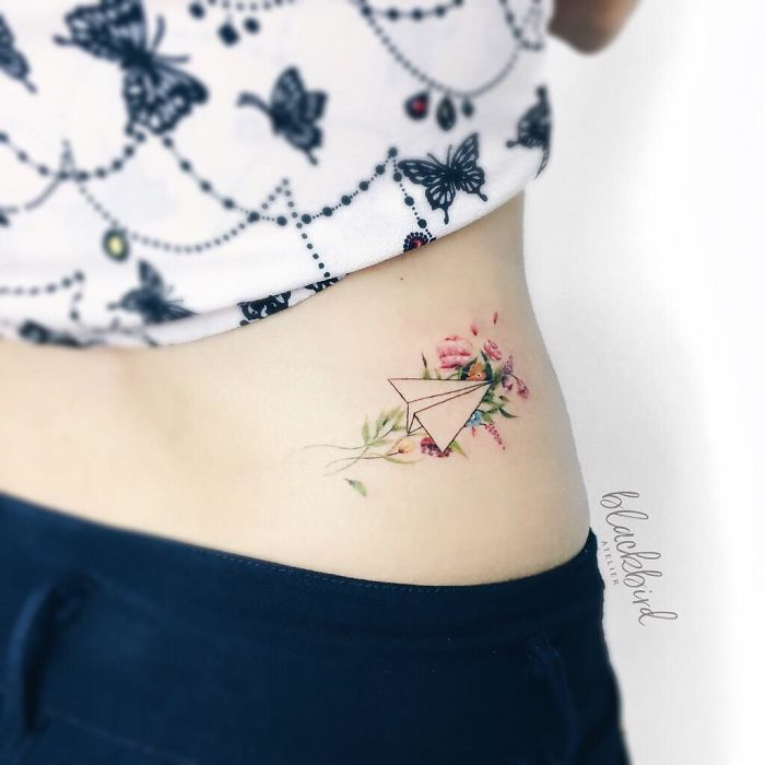 tatuagem de avião e flores