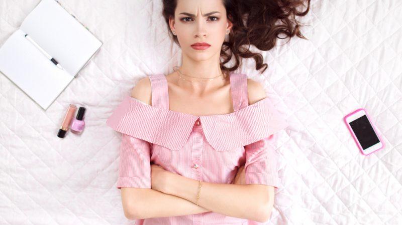mulher irritada de braços cruzados deitada na cama