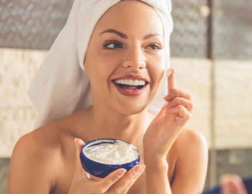mulher passando hidratante no rosto