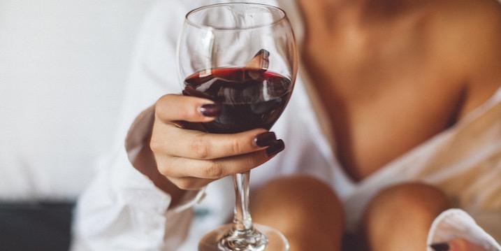 mulher segurando taça de vinho