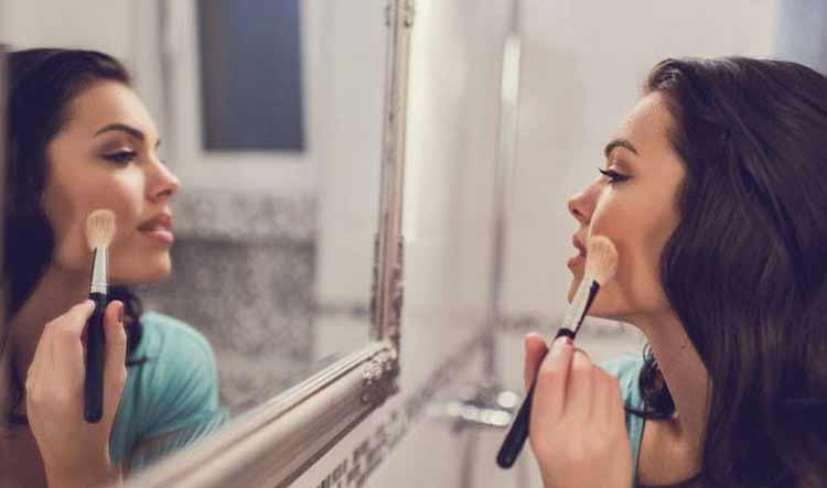 mulher-se-olhando-no-espelho-e-se-maquiando