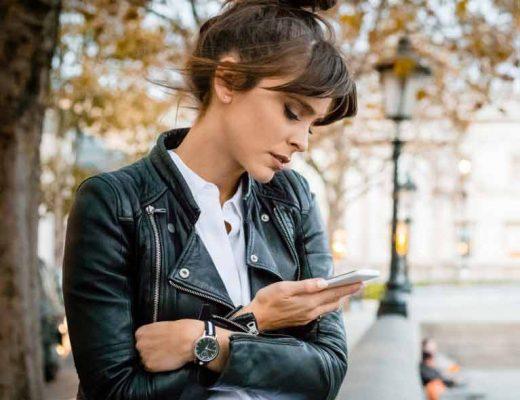 mulher-olhando-no-celular-camisa-branca-e-jaqueta-de-couro-preta