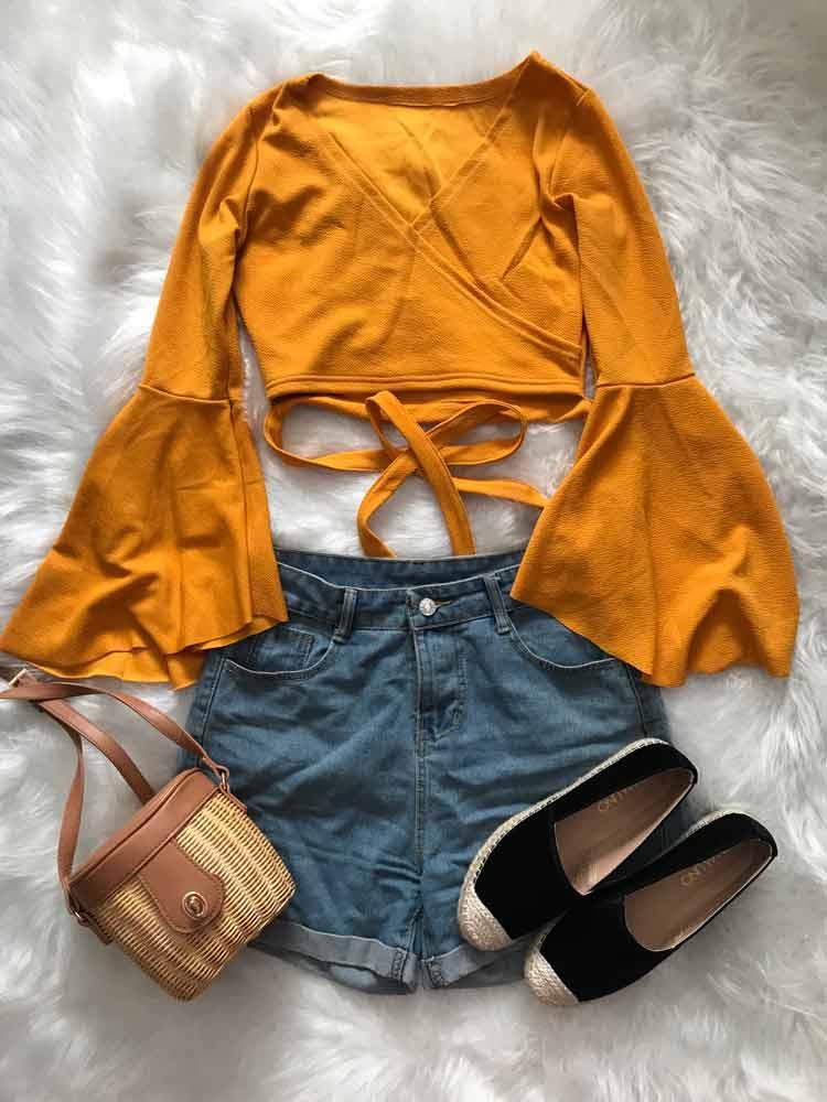 blusa-amarela-manga-sino,-shors-jeans-e-bolsa-de-palha