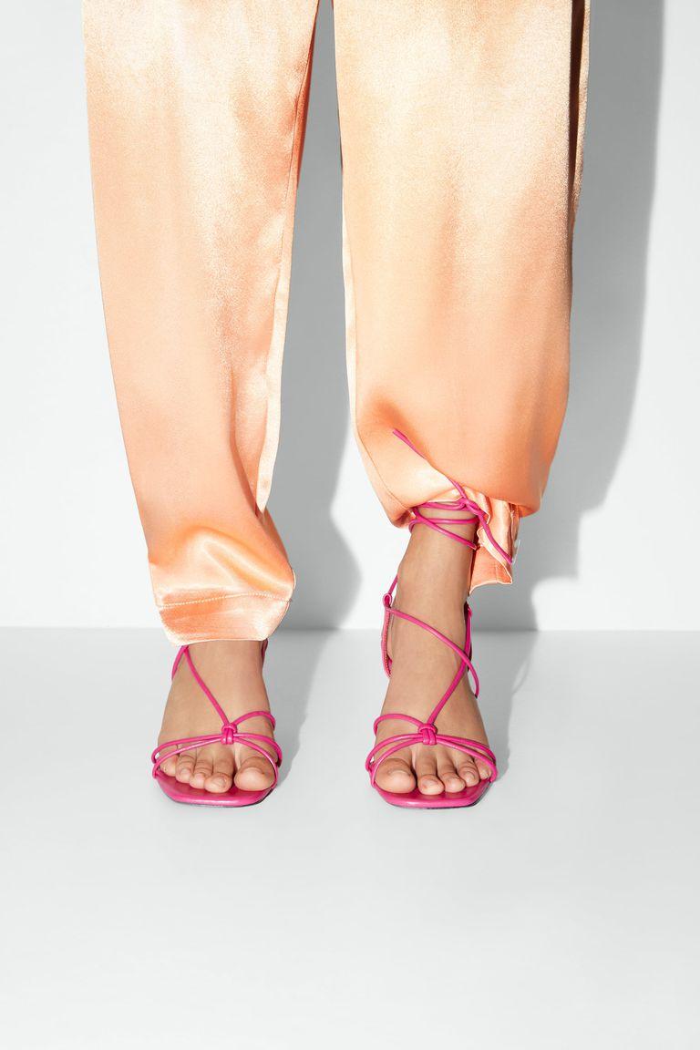 sandália amarrada por cima da calça