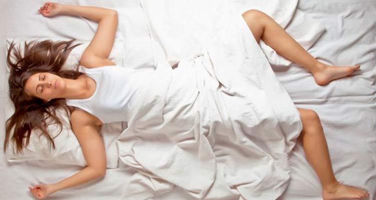 mulher-dormindo-com-braços-e-pernas-abertas