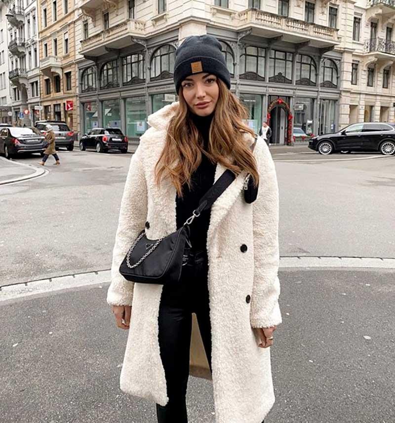 casaco-pelinhos-branco-bolsa-preta-curzada-no-corpo-touca-preta-na-cabeca