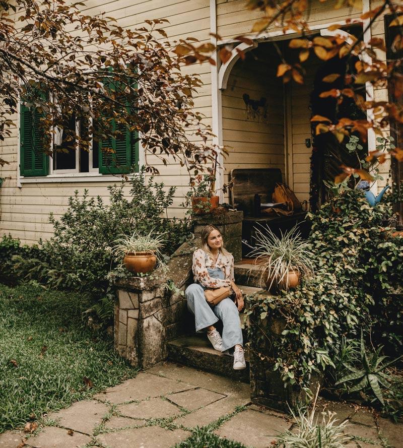 mulher-sentada-na-frente-de-casa