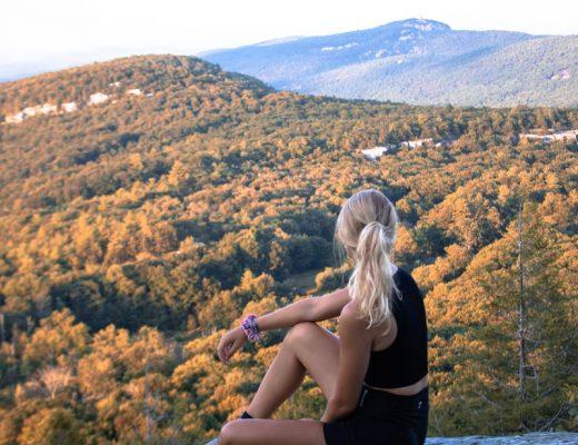 mulher-solteira-loira-sentada-na-pedra-horizonte-natureza
