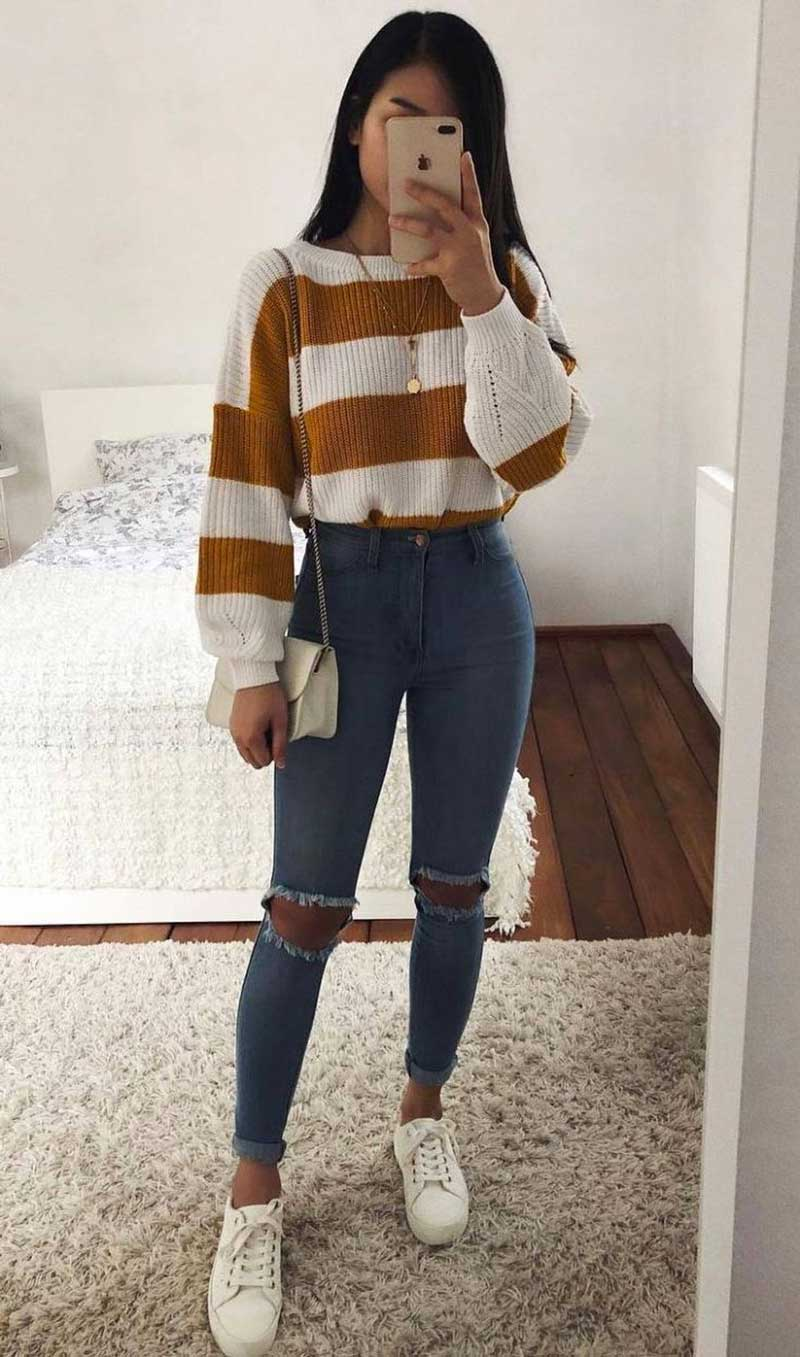 calça jeans skinny rasgada no joelho suéter de la tênis branco